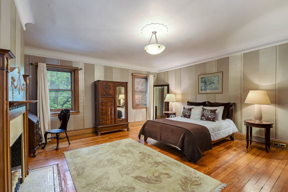 This primary bedroom has a large dark brown bed that stands out against the light beige walls and hardwood flooring that is topped with a large area rug. The floor matches well with the wooden dresser on the side flanked by windows.