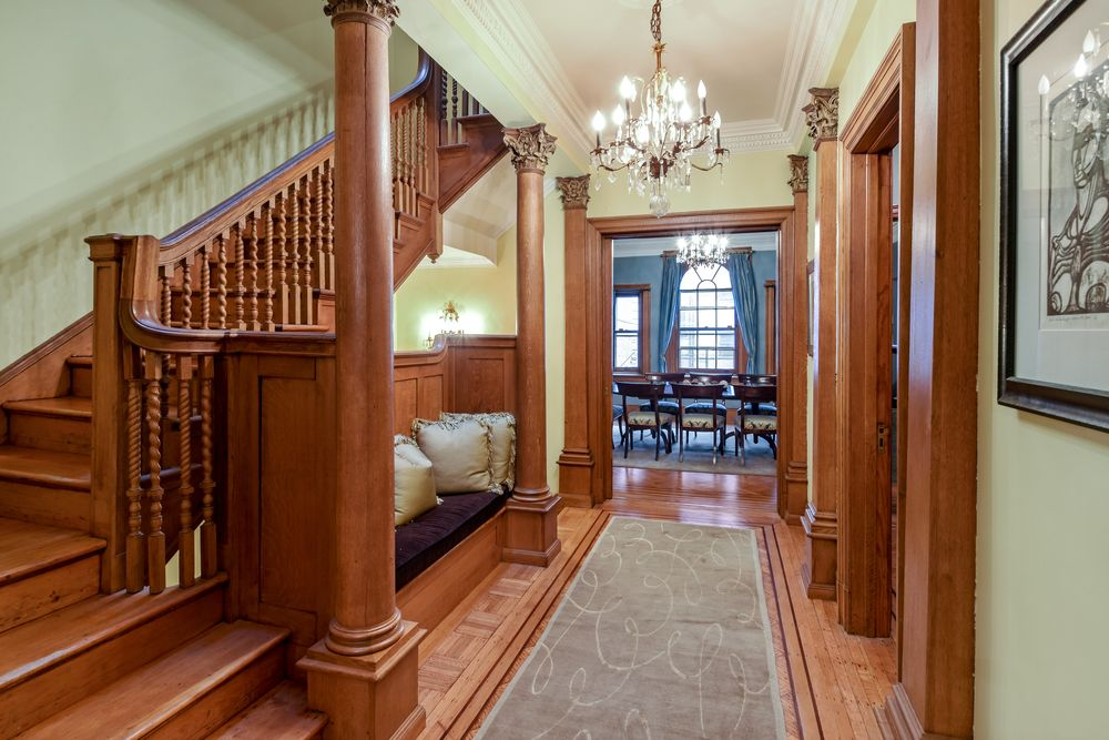 This is the charming and simple foyer with matching wooden wainscoting, pillars and railing of the staircase. These are then complemented by the chandelier from the tray ceiling and the built-in cushioned bench on the side.