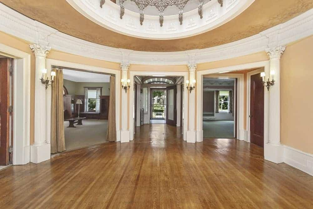An empty entry foyer with beige walls and has classy wall lights and a stunning dome ceiling.