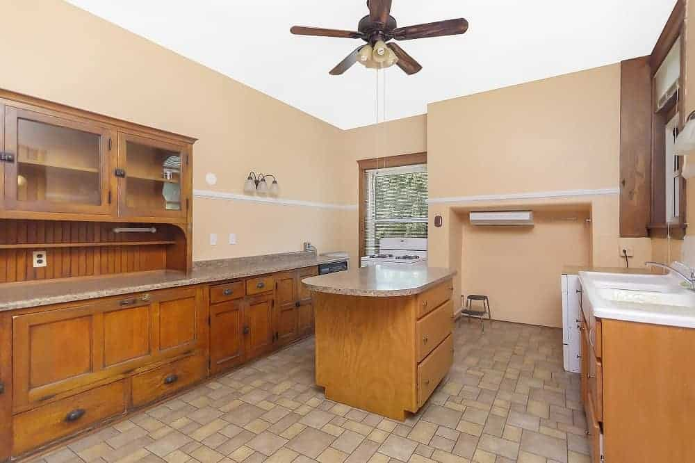 An empty kitchen featuring a granite countertop and a center island, along with a sink counter on the side.