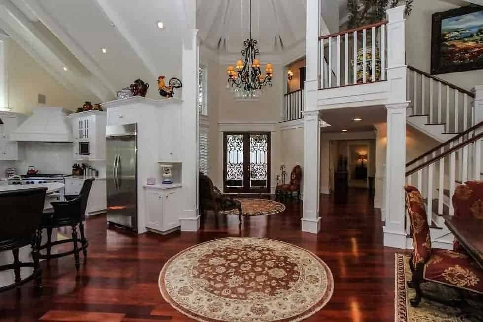 This is a view of the foyer on the far side coming in from the glass doors. This tall area is topped with a chandelier and leads to the open-style interiors of the house.