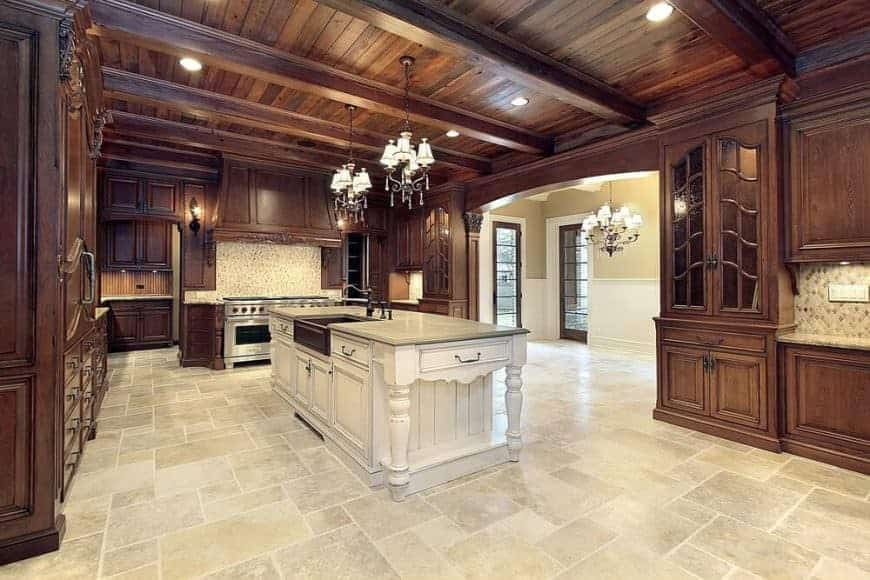 This spacious and airy kitchen is dominated by the brown wooden elements of the shilap plank ceiling with exposed wooden beams and the brown wooden shaker cabinets and drawers of the same hue. This is balanced by the light beige marble flooring that blends well with the wooden kitchen island under two small chandeliers.