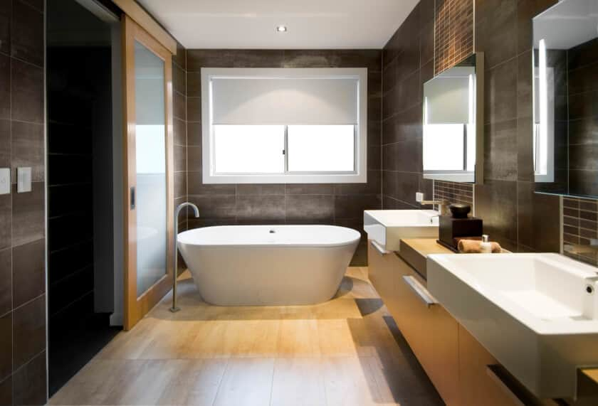 Master bathroom boasting brown tiles walls and hardwood flooring. It offers a floating vanity with two large vessel sinks along with a white freestanding tub.