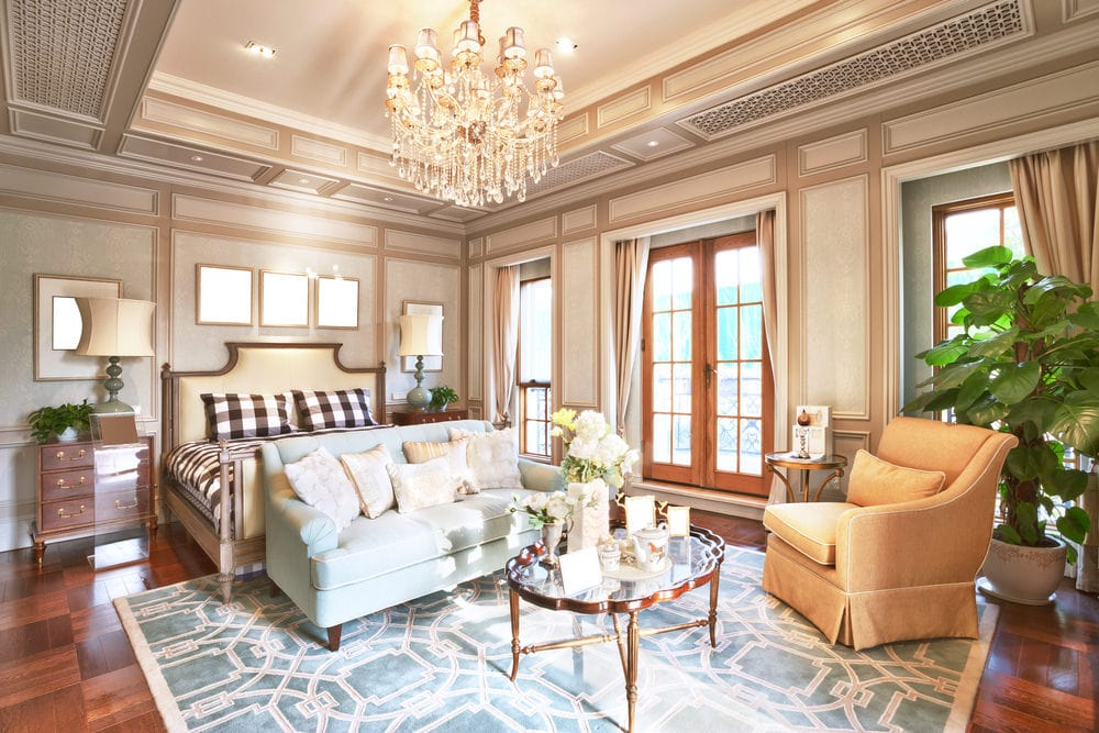 Deluxe primary bedroom boasts a cozy bed and a sitting area over the blue patterned rug lighted by a fabulous crystal chandelier. It has dark hardwood flooring and brown wainscoted walls extending to the gorgeous tray ceiling.