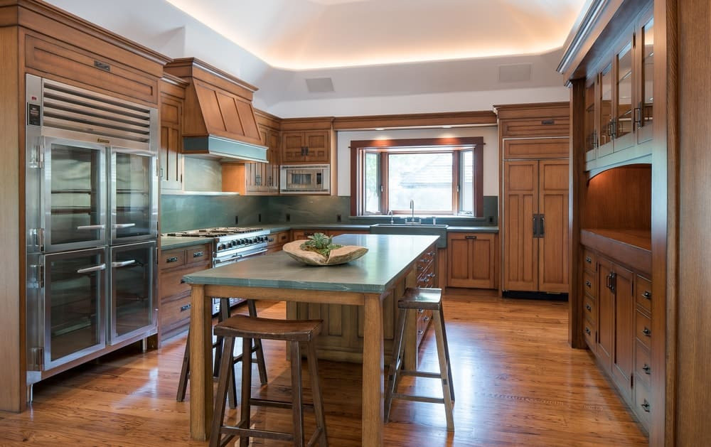 Kitchen featuring a tray ceiling and hardwood flooring matching the brown kitchen cabinetry and drawers.