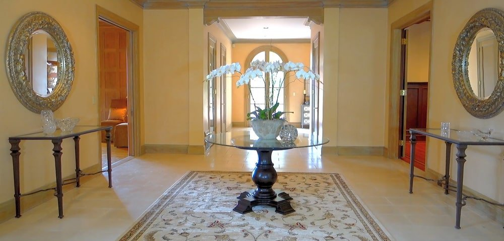 Upon entry of the house, you are welcomed by this foyer with a round glass-top table in the middle flanked by console tables topped with round mirrors.