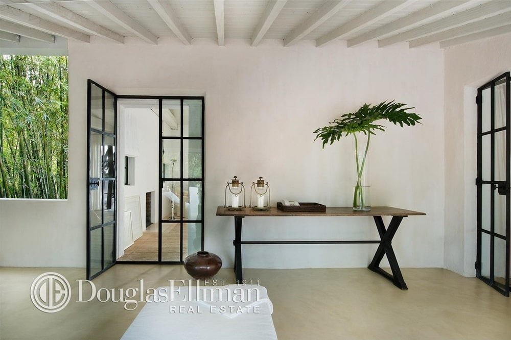 Upon entry of the house, you are welcomed by this bright and white foyer with a console table on the side of the French glass door.