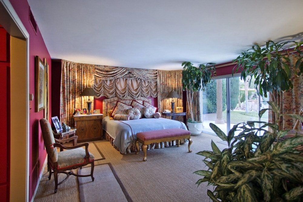 This brilliant primary bedroom has red walls adorned with floral curtains that pair well with the luxurious bed. These are then complemented by the potted plants.