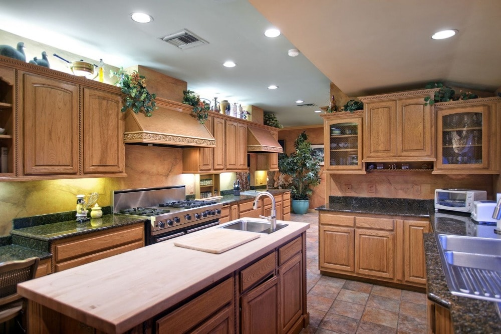 This kitchen has a homey feel to its brown cabinetry and terracotta flooring tiles. These elements are adorned with well-placed potted plants and decorations.