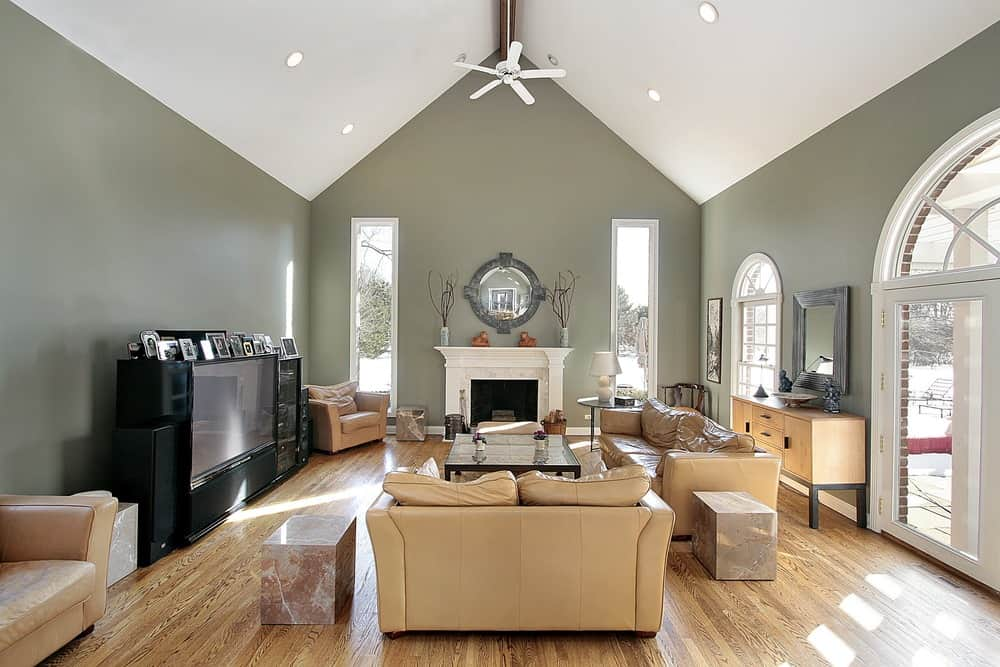 Natural light streams in through the glazed windows in this large living room with natural hardwood flooring and a towering cathedral ceiling lined with a dark wood beam. It offers beige furniture and modern appliances topped with photo frames.