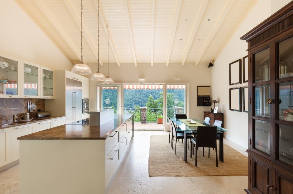 An eat-in kitchen with limestone flooring and glass sliders that open to the balcony with a breathtaking view. It includes a shiplap ceiling with exposed wood beams mounted with glass dome pendants.