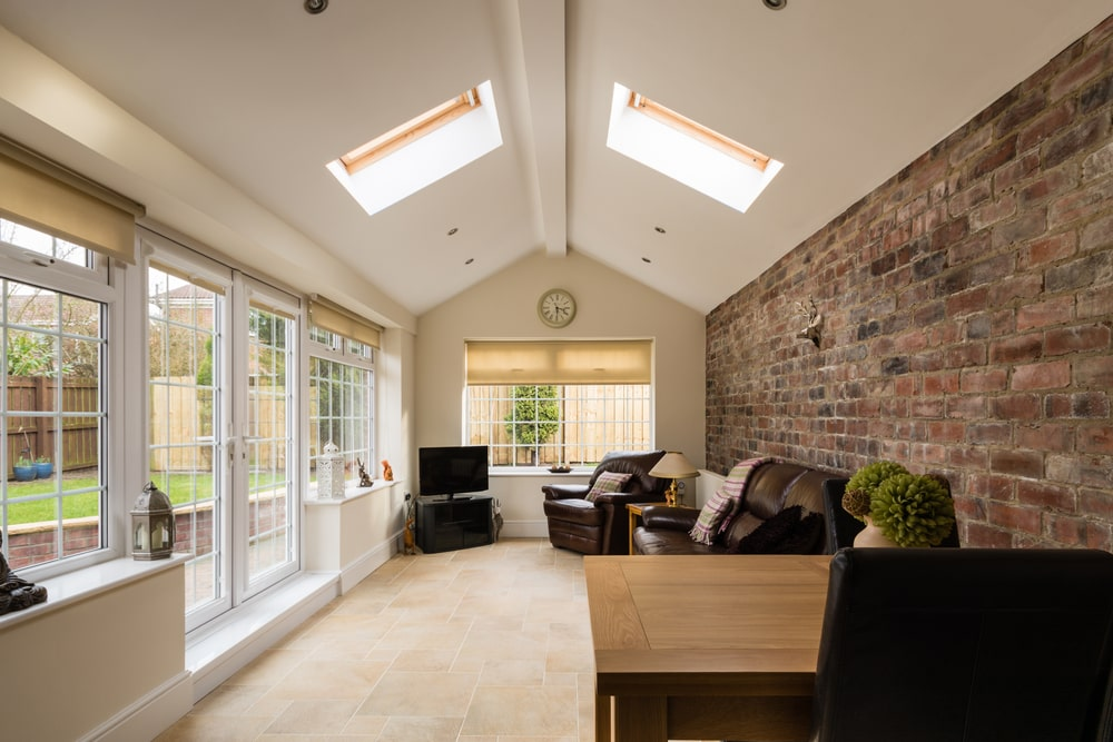 A stone brick accent wall adds texture in this narrow living room with beige limestone flooring and a cathedral ceiling lined with an exposed beam in the middle. It is fitted with skylights which invite natural light in along with French door and windows.