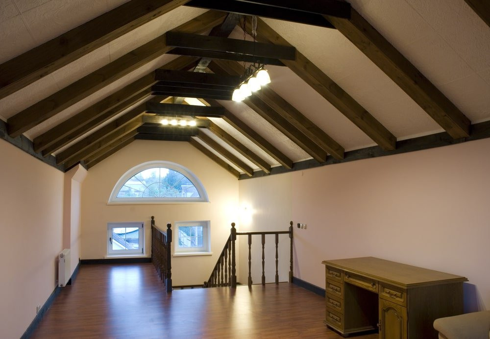 A cozy attic with a cathedral ceiling covered in A-frame beams. It balances the almost empty room with its busy features.