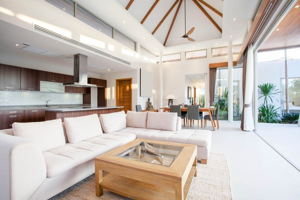 An abundance of natural light flows in through the panoramic windows in this white, bright house with tile flooring and a high ceiling accented with exposed wood beams.