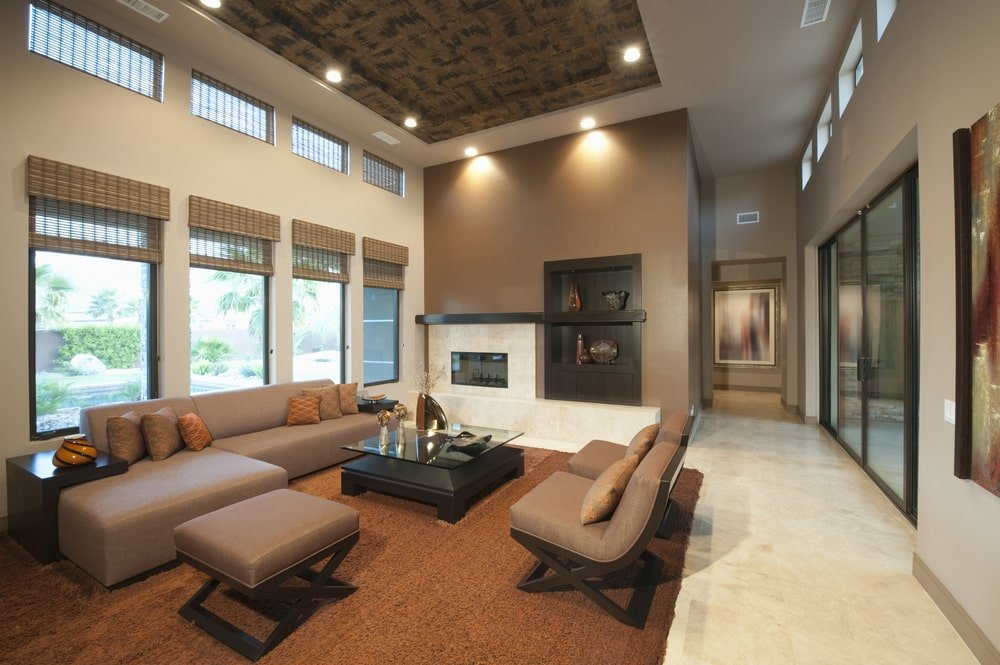A marvelous tray ceiling adds character in this beige living room with marble tile flooring and glazed windows covered in wicker roman shades. It is furnished with leather seats and a glass top dining table that sits on a brown area rug.