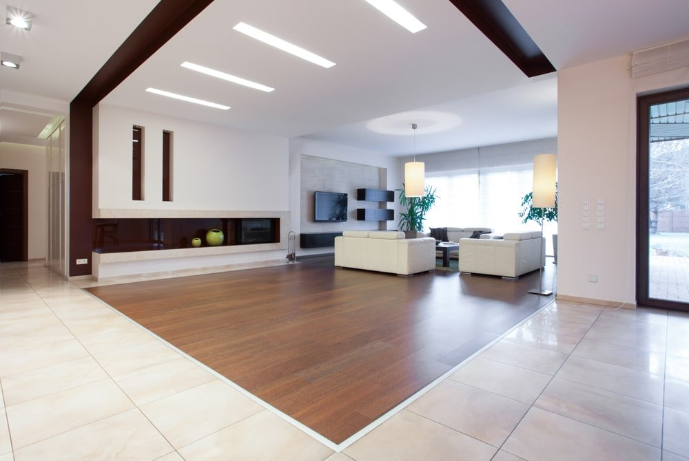 An expansive living room with a regular white ceiling fitted with linear recessed lights. It includes full height glazing and natural hardwood flooring which transitions to a marble tile flooring.