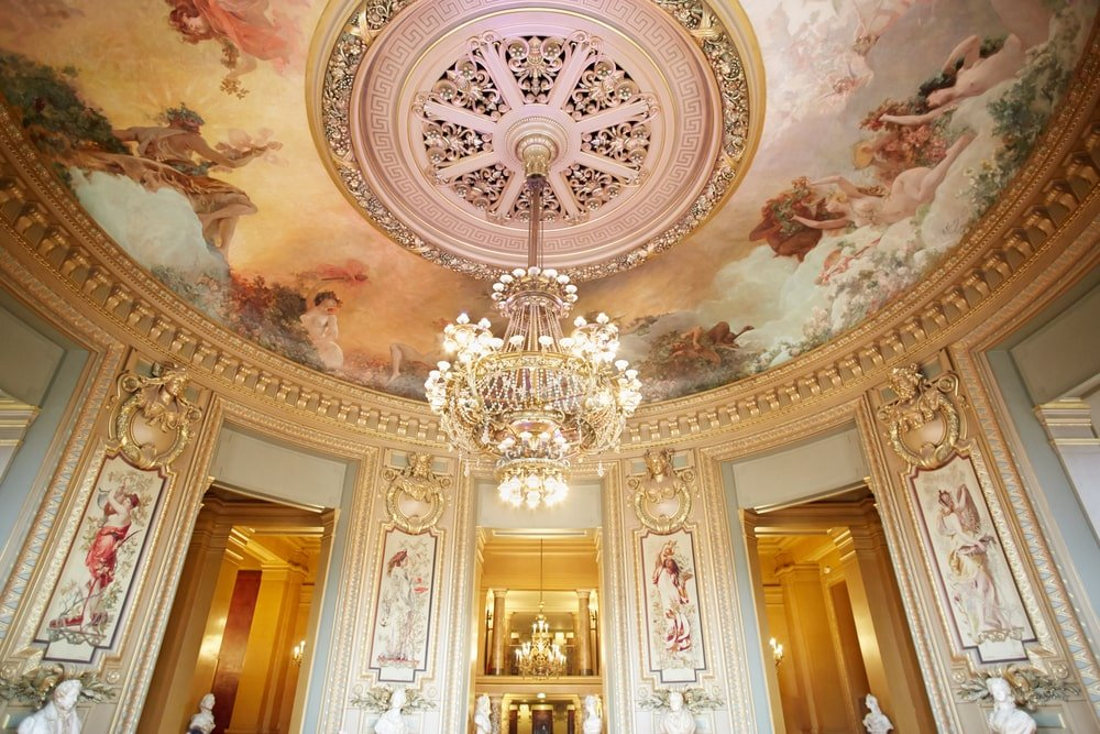 An elegant dome ceiling painted in large scale mural of gorgeous goddesses extending to the columns for a cohesive look. It is fixed with a fabulous grand chandelier that goes well with the intricate medallion.
