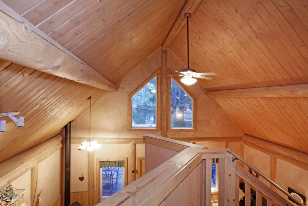 A closer look at this cathedral ceiling that's clad in wood planks and lined with round beams. You can feel the warmth and coziness it brings as the beams extend to the walls and complement other wooden elements.