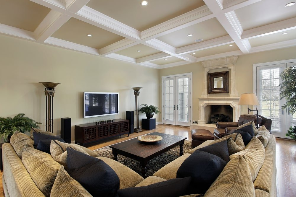 The striking coffered ceiling stands out in this living room with beige walls and natural hardwood flooring topped by a classic rug. Even though the ceiling is quite low, green potted plants bring the airy ambiance in the room along with natural light from the French doors.