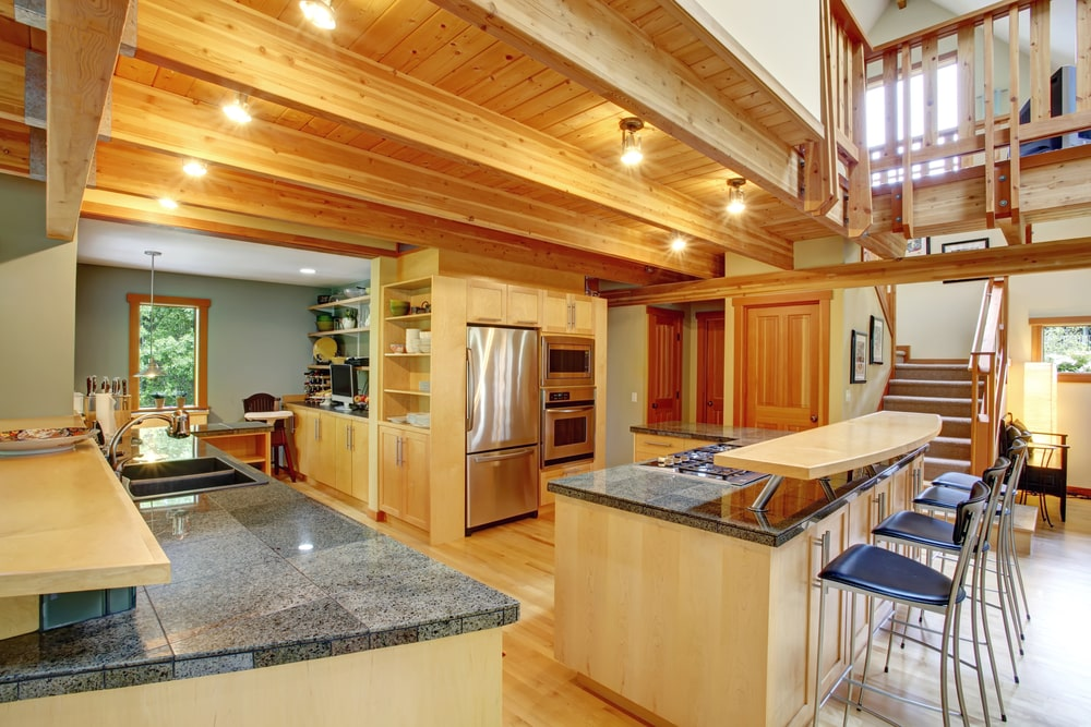Cozy kitchen with a wood beam ceiling that complements the wooden cabinetry and light hardwood flooring. It is equipped with stainless steel appliances that add subtle contrast to the room.