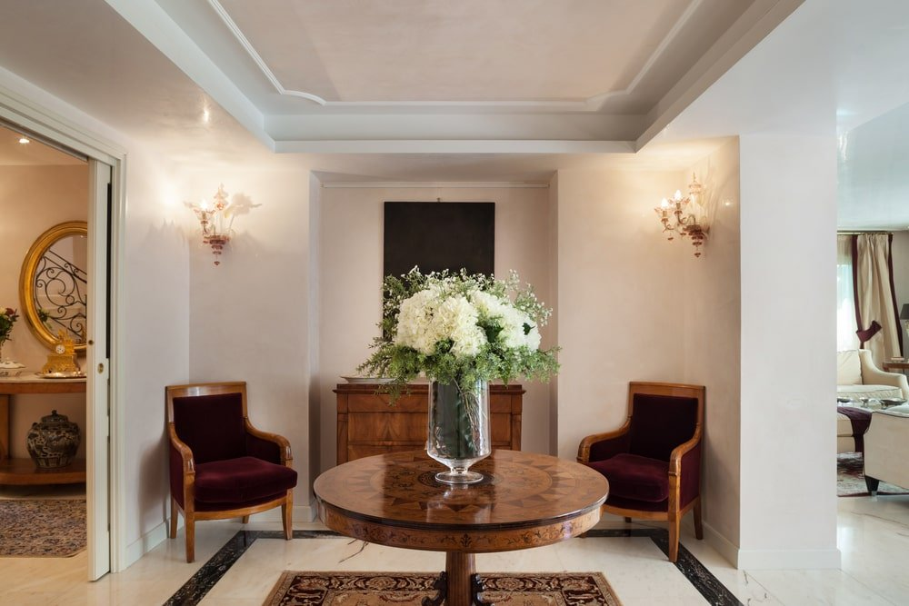A pair of lovely candle sconces and velvet armchairs create perfect symmetry in this sleek foyer with wooden furniture and a classic area rug over marble flooring. It boasts a double tray ceiling that can double as an added shelf.