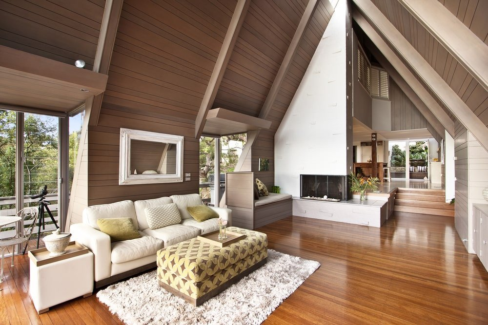 A cozy living room features a pointed cathedral ceiling that's clad in wood planks extending to the walls. It is fitted with a skylight that allows natural light in.