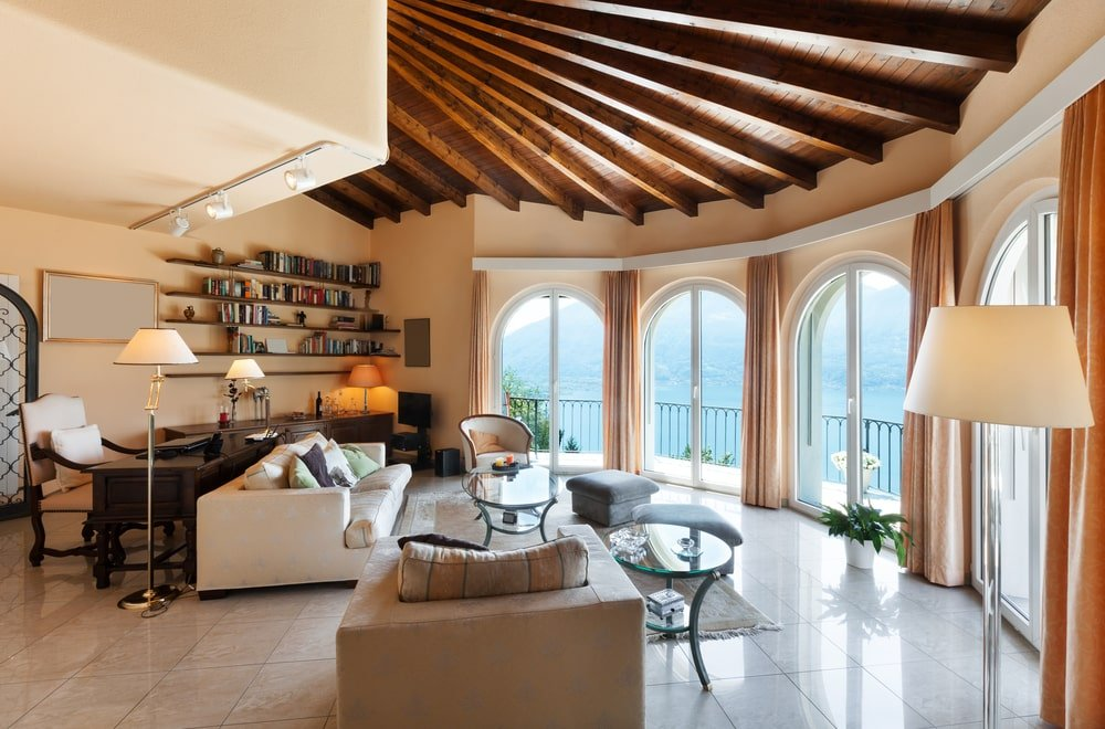 Wood beam ceiling is the highlight of this home office with a living space facing the arched French doors leading out to the balcony with a spectacular mountain view. It complements the floating shelves that are filled with various books.