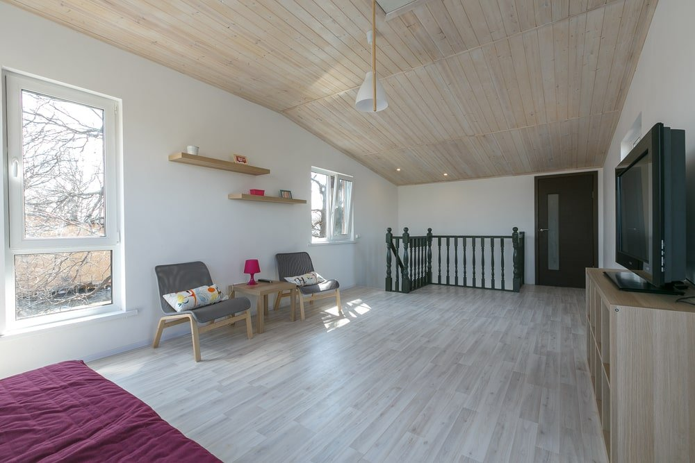 A spacious attic with white walls and a vaulted ceiling clad in wood planks. It complements the hardwood flooring and wooden furniture resulting in a light and airy look.