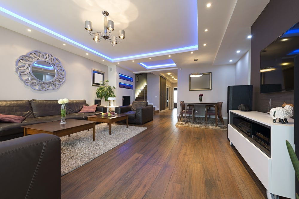 This house features luminous tray ceilings surrounded by strip lights and recessed lights. It is a great highlight in this sleek, modern house with white walls and dark hardwood flooring.