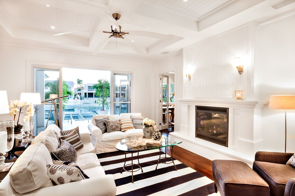 Bright living space with beadboard walls and a matching coffered ceiling mounted with a sleek fan. It is beautifully contrasted with a rich hardwood flooring that's topped by a striking striped rug.