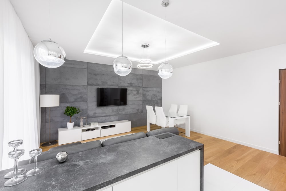 This modern house features sleek furniture and gorgeous lightings that hung from the white tray ceiling. It has light hardwood flooring and a gray paneled accent wall that matches the marble counter.