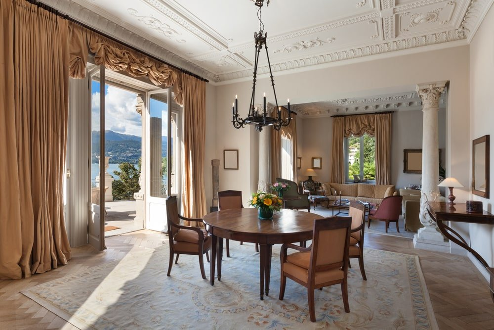 This is an open concept house with herringbone wood flooring and an ornate ceiling with intricate detailing. It complements well with the marble columns that blend in with the beige walls.