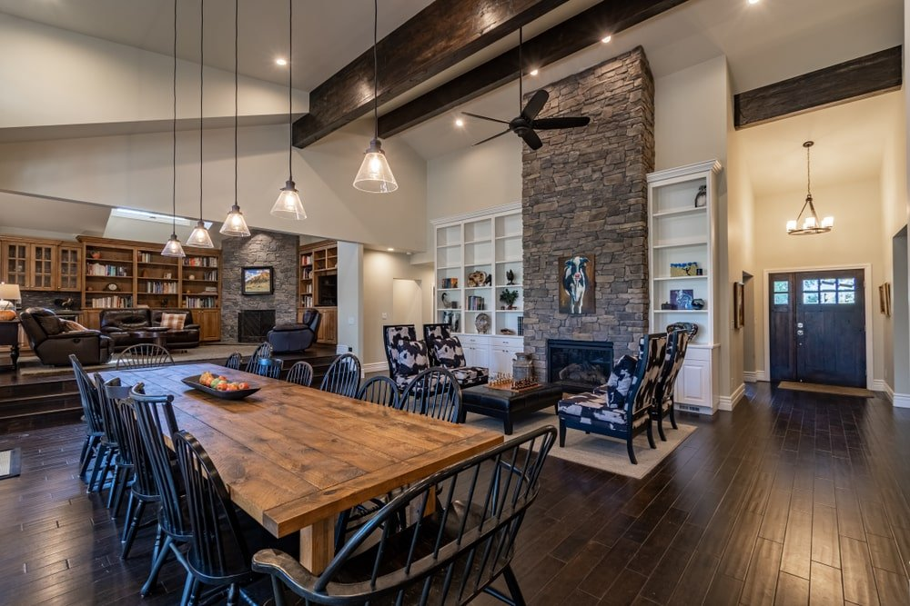 Dark wood beams create a striking contrast to the high vaulted ceiling. It is a great accompaniment to the brick fireplace which adds texture in this open concept house.