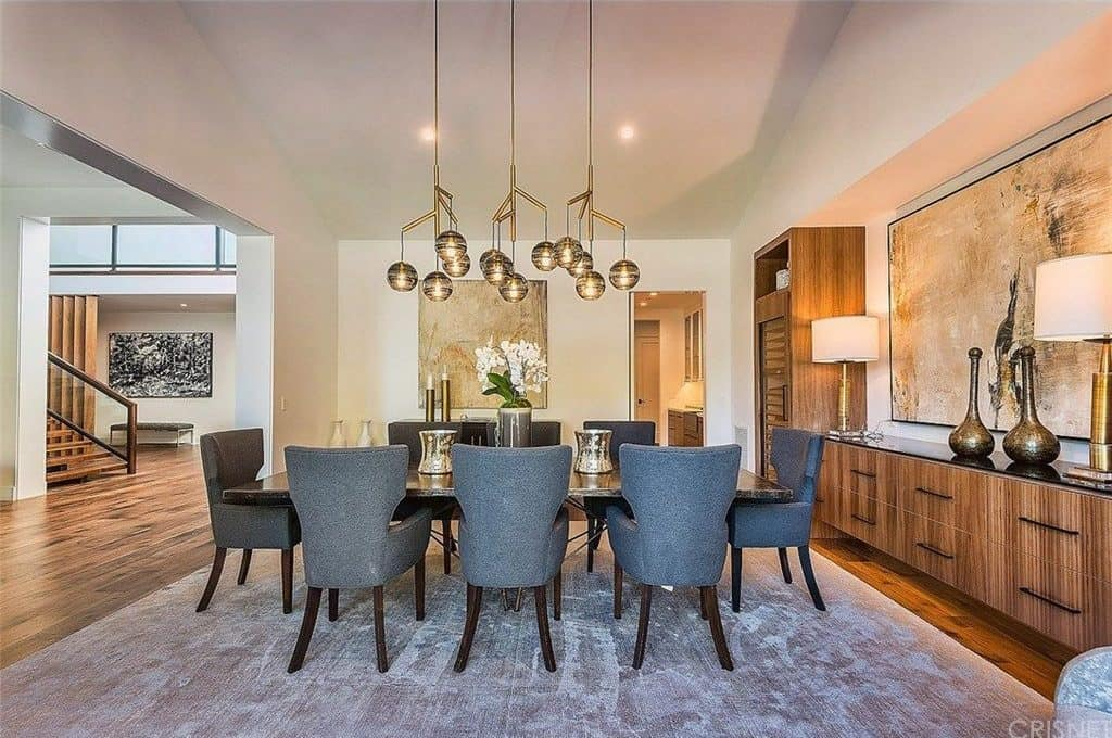 Contemporary chandeliers illuminate this dining room featuring a granite top table and gray wingback chairs over a distressed area rug. It is accompanied by large artworks and wooden buffet tables.
