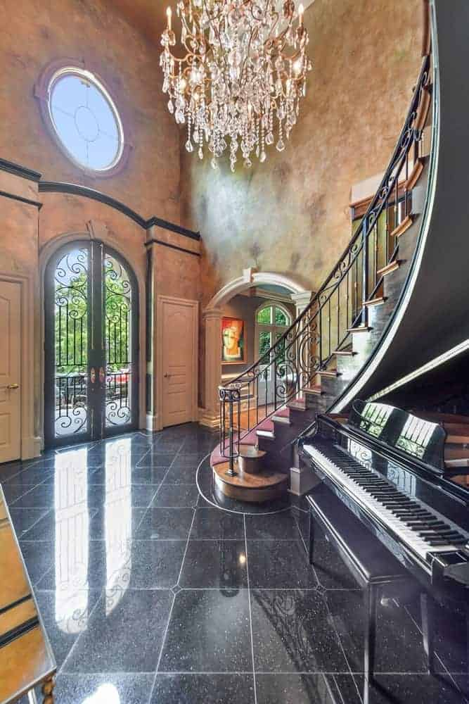 An elegant entry foyer featuring black tiles flooring and brown walls, along with a high ceiling where the luxurious grand chandelier is set.
