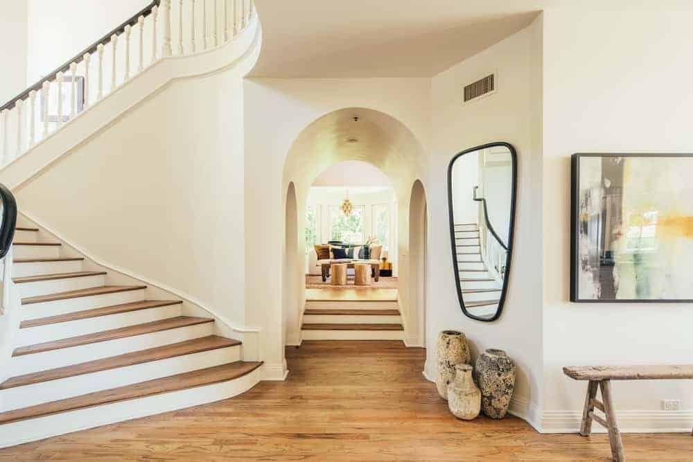 This entry of the house features white walls and hardwood floors. This entry leads to the living space. The staircase is also set on the side.