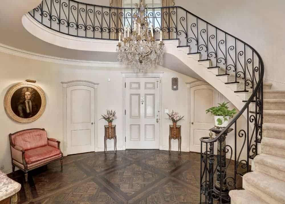 A beautiful entry foyer boasting stylish flooring and a high ceiling lighted by a luxurious chandelier lighting up the staircase.