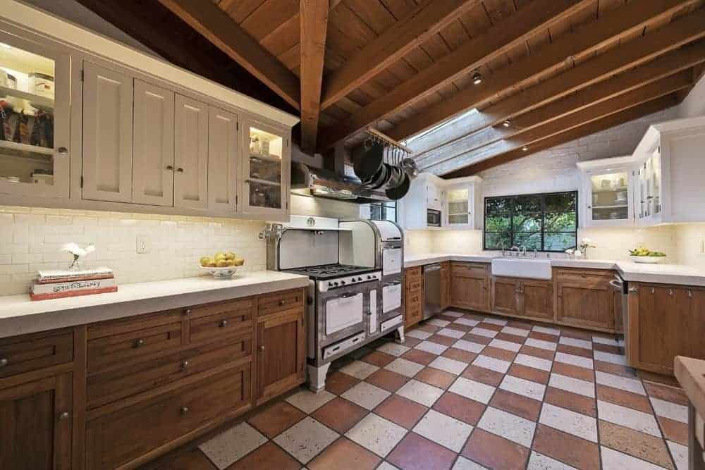 A spacious kitchen featuring a wooden shed ceiling with exposed beams along with a checker tiles flooring.