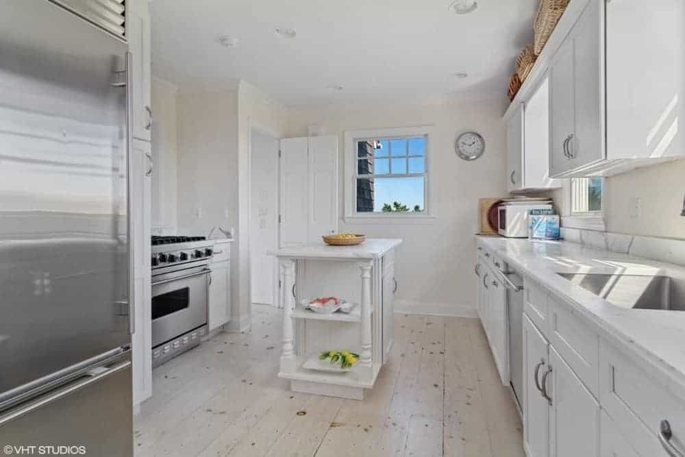 A white kitchen featuring a small white center table along with a single wall kitchen counter with a white countertop.