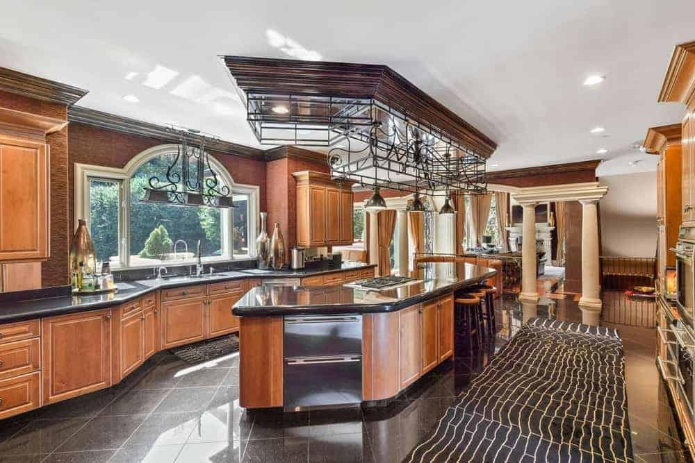 Large kitchen area boasting a custom island and kitchen counter both with black countertops and brown cabinetry.