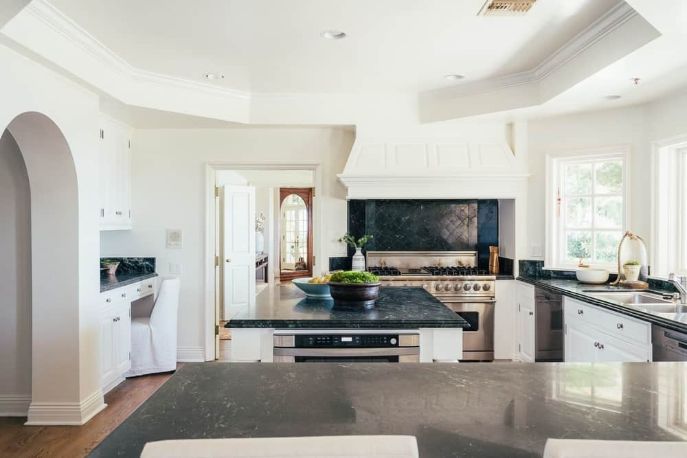 This kitchen features white walls and a white tray ceiling. The kitchen offers an L-shaped kitchen counter with a center island, both featuring black marble countertops.