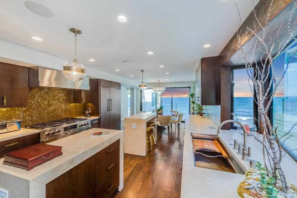 This kitchen offers two waterfall-style center islands along with hardwood flooring and a white ceiling with recessed ceiling lights.