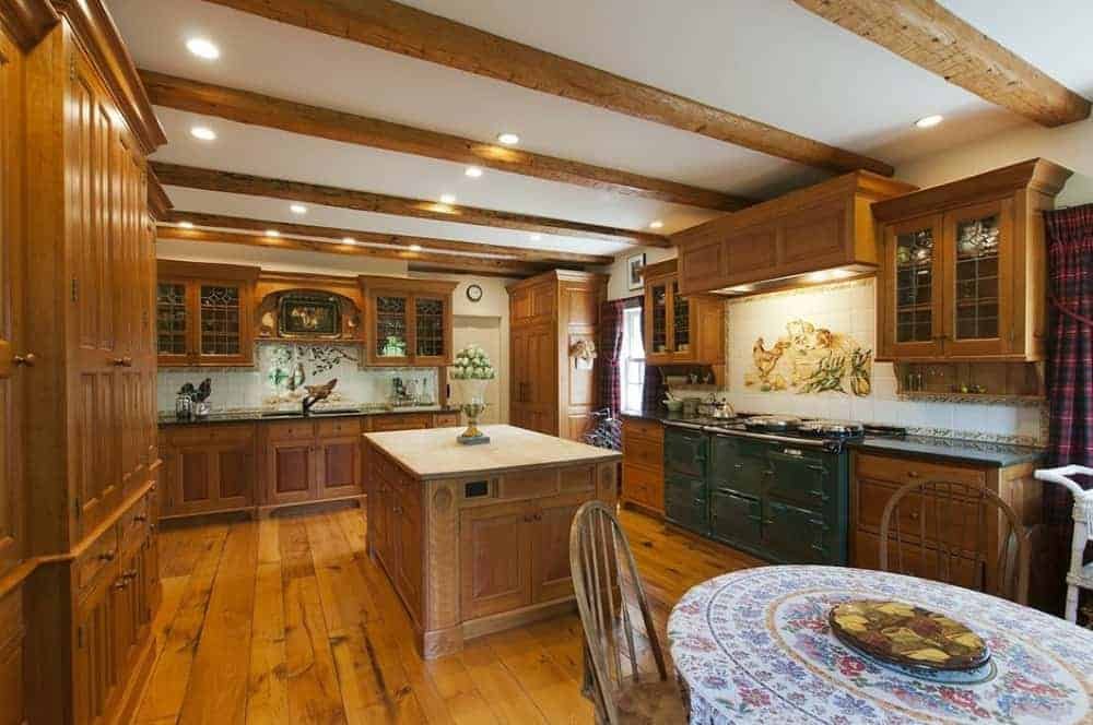 Brown kitchen featuring hardwood flooring and brown cabinetry, along with a ceiling with exposed wooden beams.