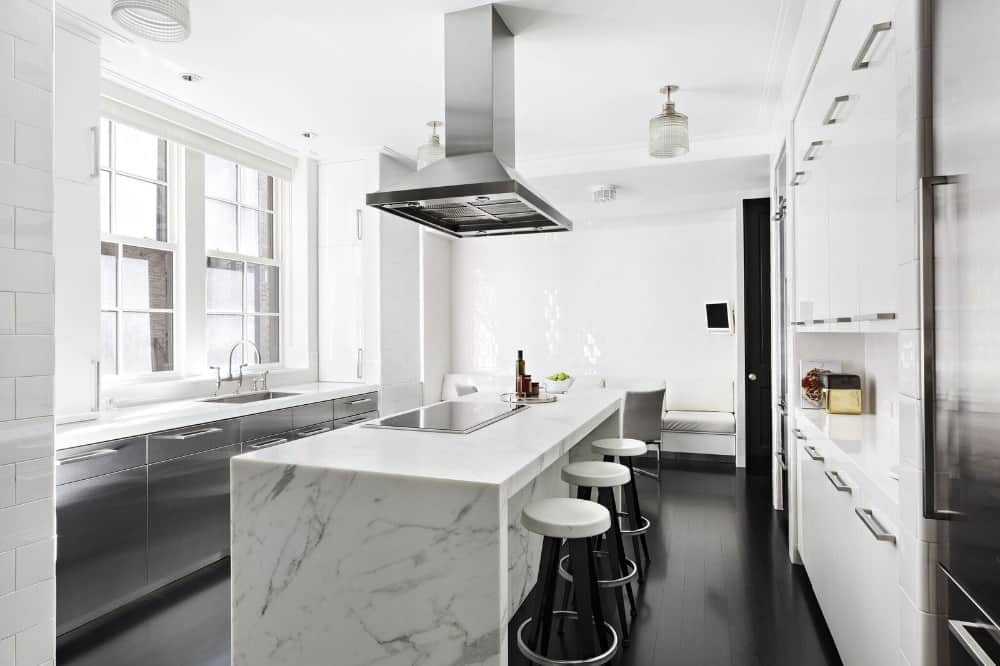 A bright kitchen boasting a large waterfall-style marble center island with space for a breakfast bar. The area features white walls and a white ceiling, along with espresso hardwood flooring.