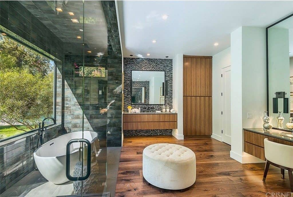 This bathroom is a celebrity-owned one, featuring hardwood floors and a white ceiling. It has a stylish walk-in shower and bathtub room featuring a large glass window. There's also a floating vanity sink and a powder desk area.