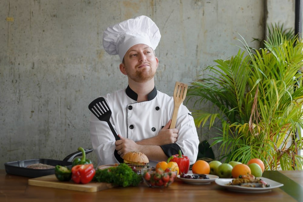 A chef holding spatulas on both hands.