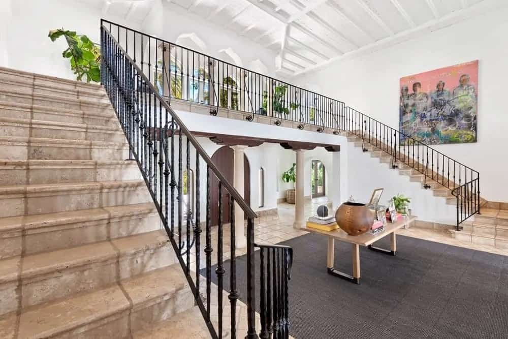 Upon entry of the house, you are welcomed by this foyer that has a large area rug, a wooden table and an indoor balcony above.