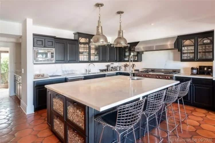 The kitchen has terracotta flooring tiles to complement the dark cabinetry of the kitchen contrasted by the white walls and ceiling.