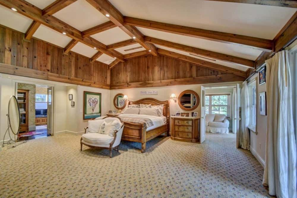 This is a spacious primary bedroom with a wooden bed to match the accents of the upper wals and the exposed wood beams of the arched ceiling.