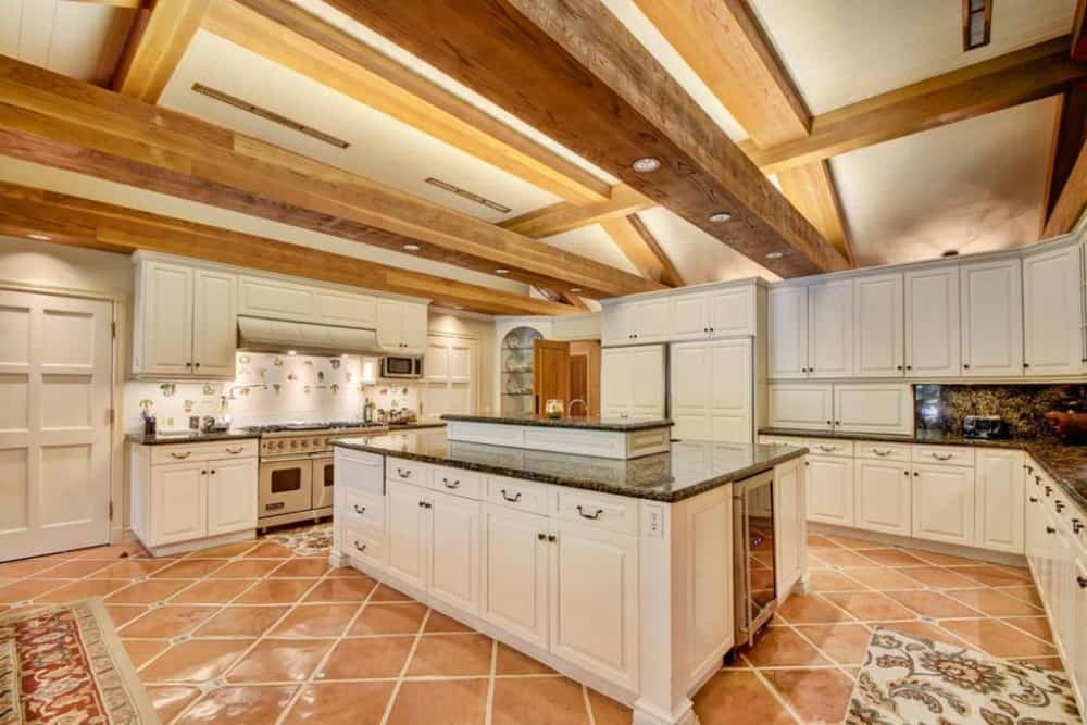This is a gorgeous kitchen with terracotta flooring tiles to complement the white kitchen island and the surrounding cabinetry topped with a beamed ceiling.
